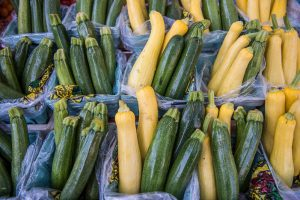 farmers market containers with green zucchini and yellow squash