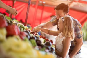 Father and daughter looking at produce at a farmers' market